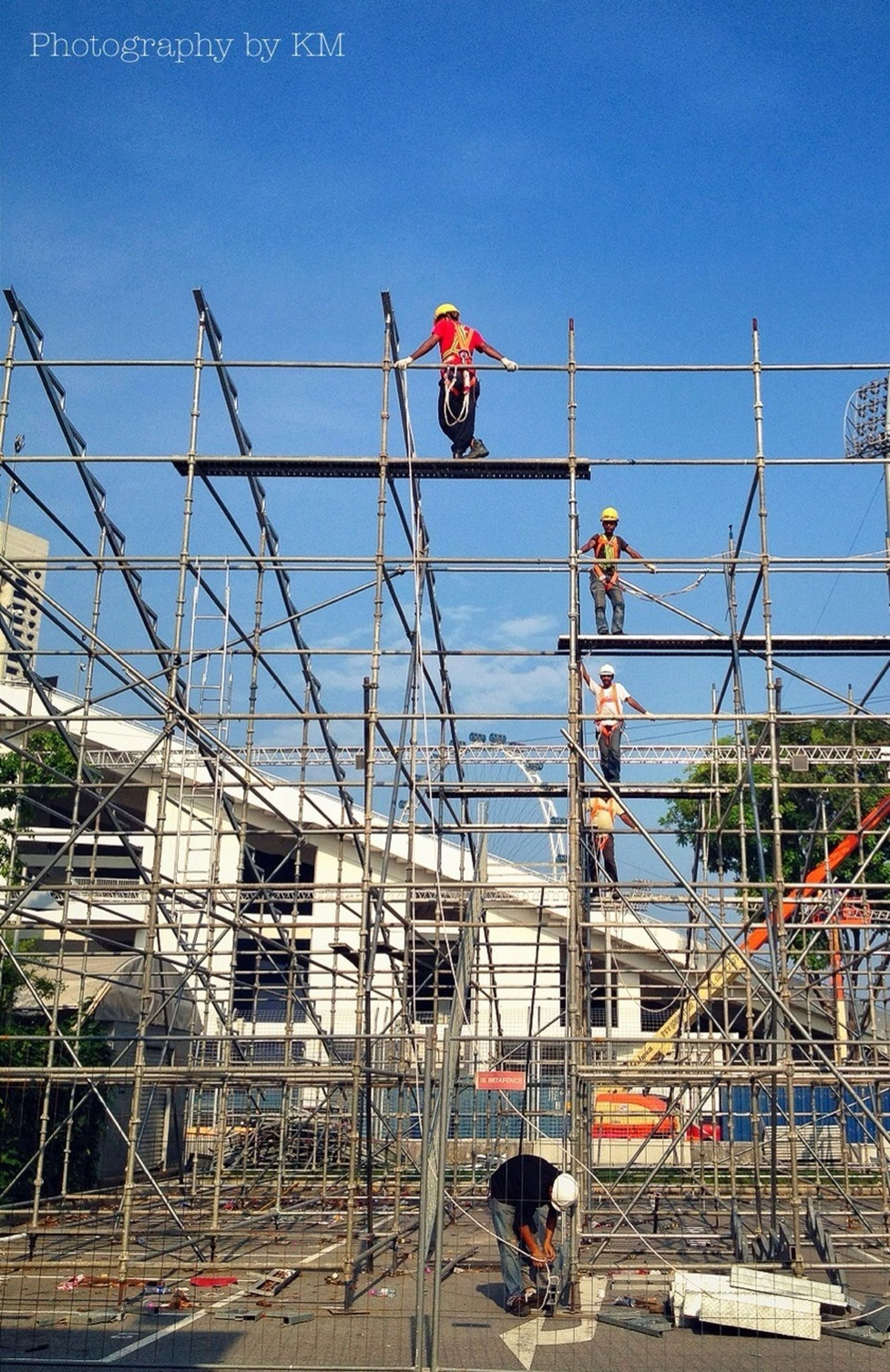 men, built structure, leisure activity, lifestyles, blue, architecture, low angle view, person, clear sky, sky, building exterior, day, transportation, occupation, working, outdoors, medium group of people