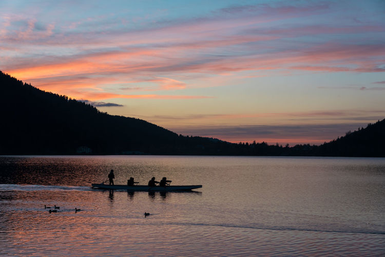 Sunset Healthy Lifestyle Lake Canoe Canoeing Water Sport Leisure Activity Silhouette Real People Medium Group Of People Duck Standing Water Water Waterfront Sport Weekend Activities Sky Nautical Vessel Beauty In Nature Scenics - Nature Transportation Nature Mode Of Transportation Cloud - Sky Tranquil Scene Rowing Mountain Tranquility Tree Outdoors Rowboat Sculling