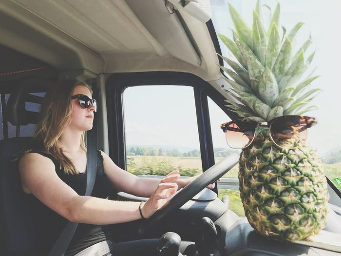 Young woman sitting in car with pineapple