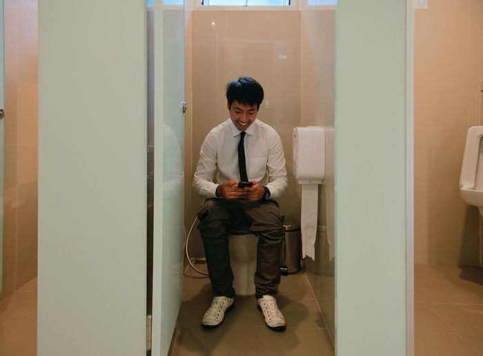 An Asian business man pooping and using smartphone in bathroom, person Chair Day Front View Full Length Indoors  Looking At Camera One Person People Pooping Portrait Real People Sitting Young Adult