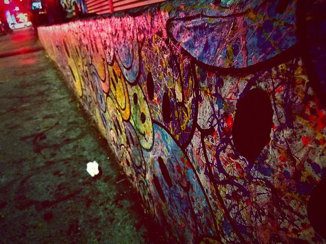 Multi Colored Outdoors No People Close-up Vibrant Colors Illuminated Night Enjoyment Graffiti Paint Mural Smiley Smiley Faces Sidewalk Street Nightlife Parallel Lines Pavement Happiness Happy Painted Wall Concrete City