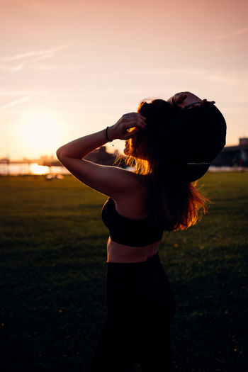 Full length of woman standing on field against sky during sunset