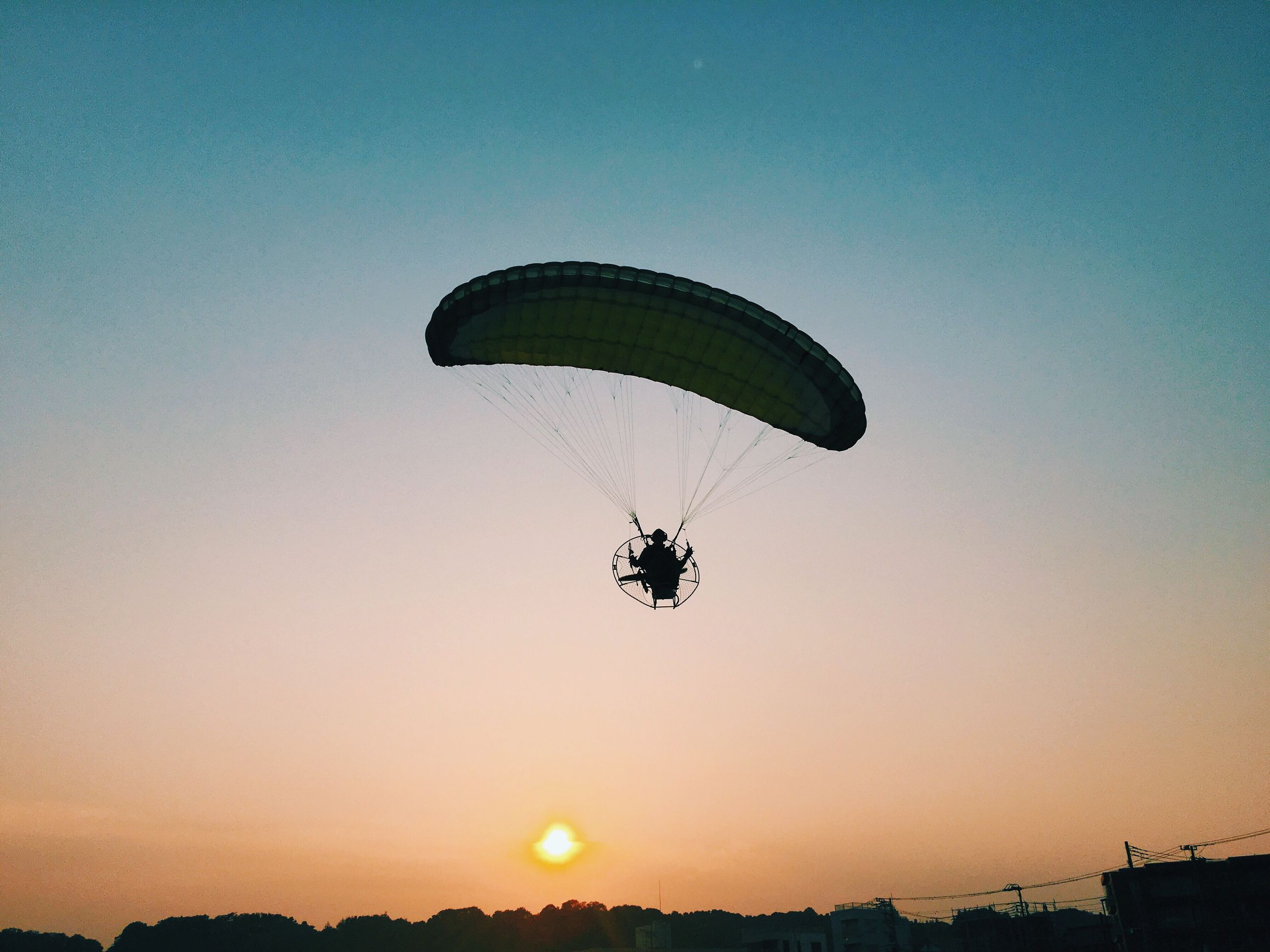clear sky, mid-air, parachute, low angle view, extreme sports, adventure, leisure activity, copy space, flying, sport, silhouette, sunset, hot air balloon, lifestyles, fun, unrecognizable person, transportation, paragliding