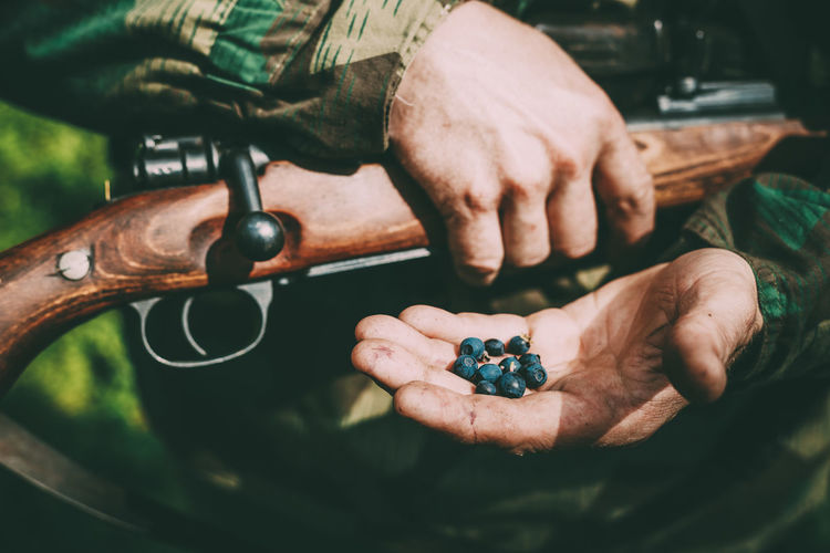 Midsection of army solider holding berries while standing outdoors