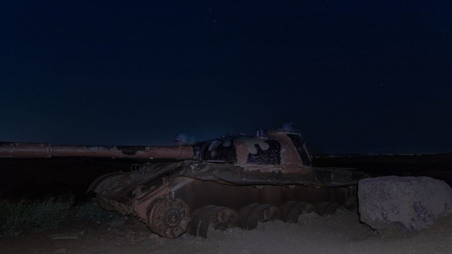 Abandoned truck on field against sky at night