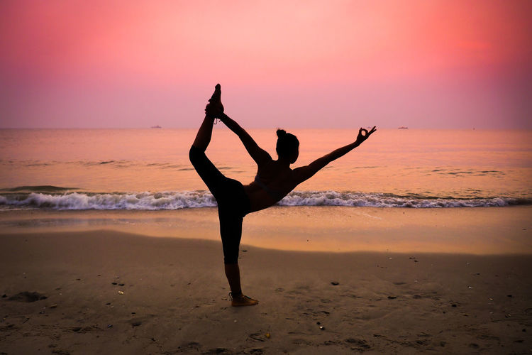 Full Length Of Silhouette Woman Practicing Yoga At Beach Against Dramatic Sky During Sunset