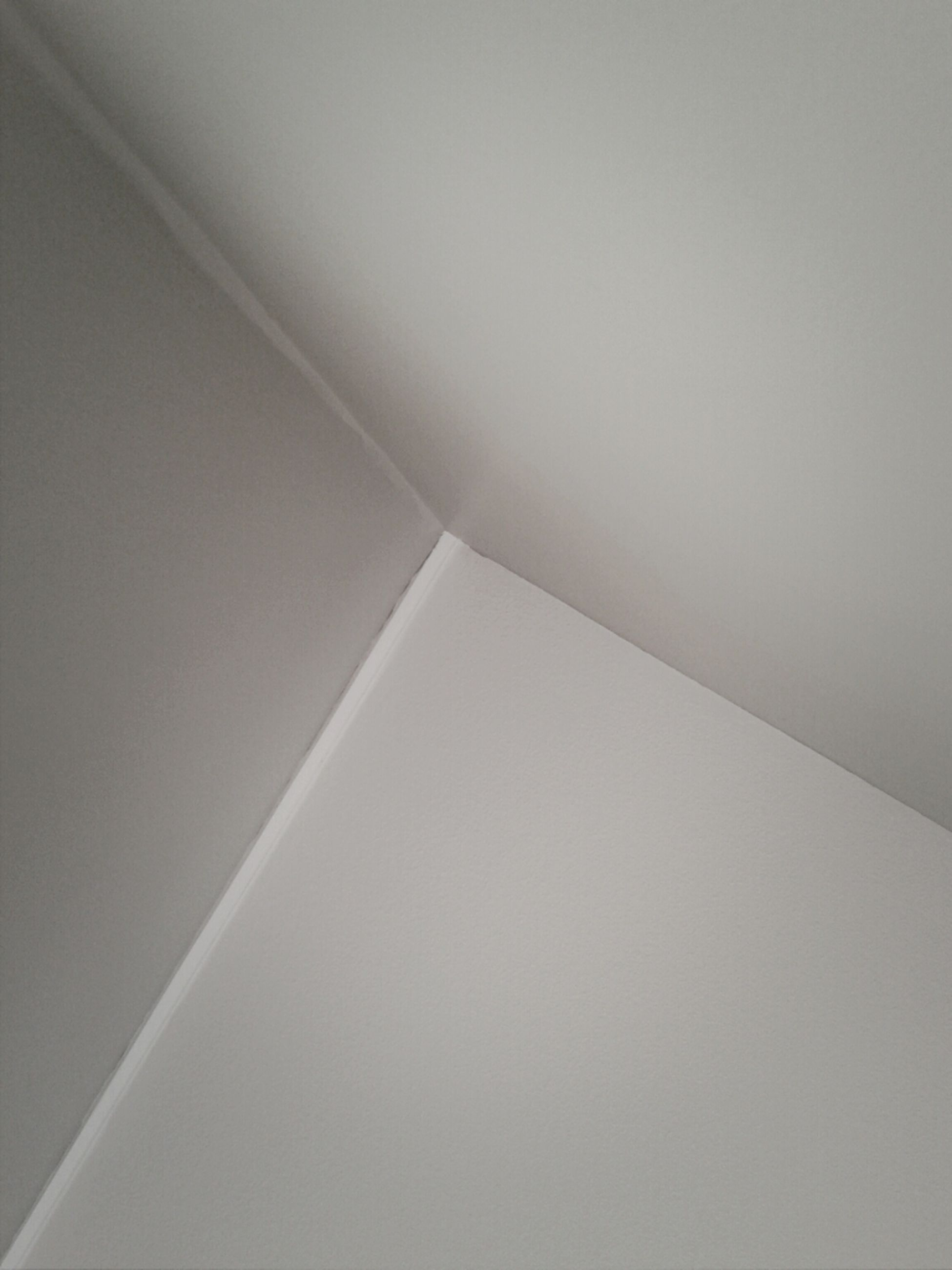 low angle view, architecture, built structure, indoors, copy space, wall - building feature, no people, day, pattern, ceiling, white color, wall, backgrounds, building, part of, sunlight, clear sky, directly below, close-up