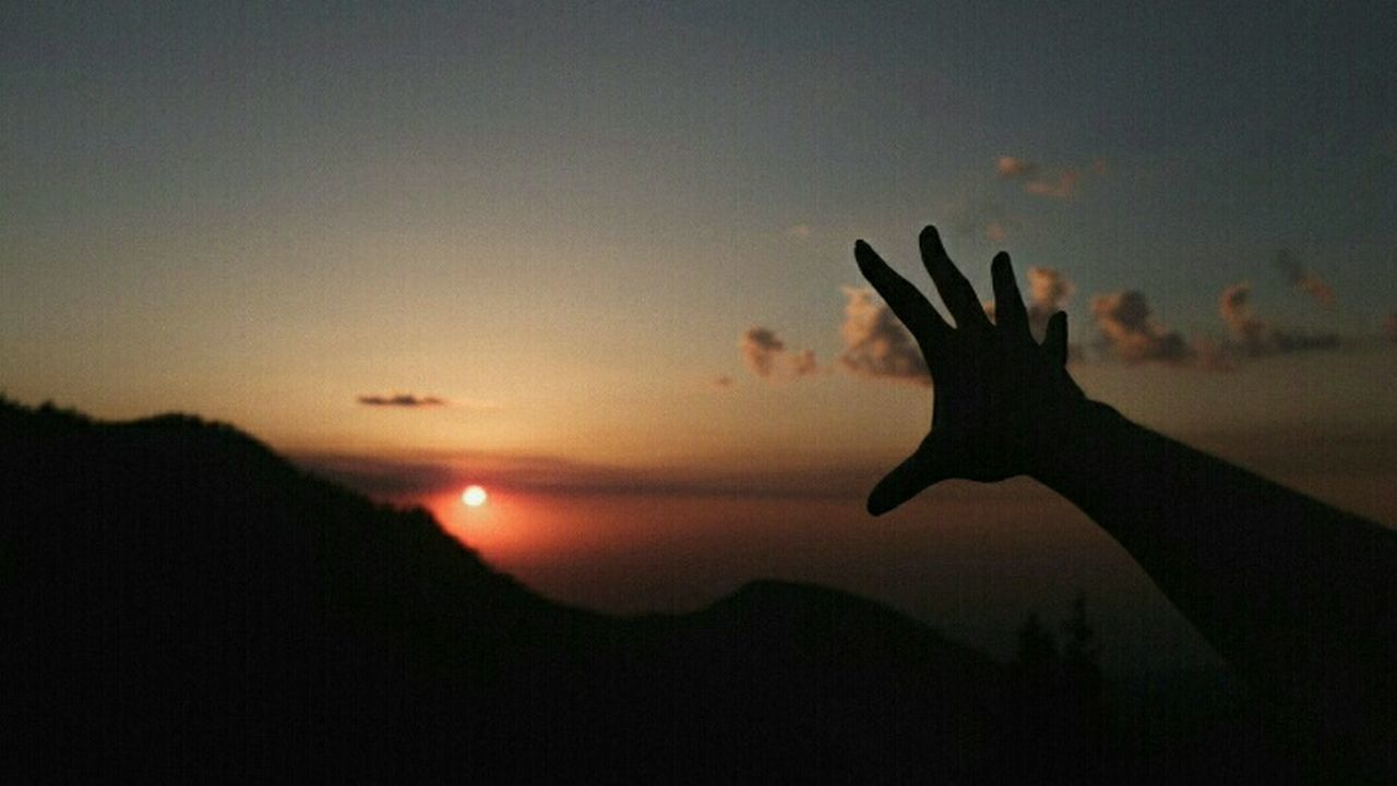 silhouette, human hand, sunset, sky, nature, one person, human body part, sun, outdoors, real people, focus on foreground, beauty in nature, scenics, close-up, day, people