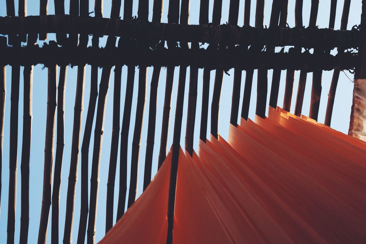 Low angle view of textiles hanging on bamboos