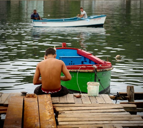 Rear view of people sitting on wooden pier