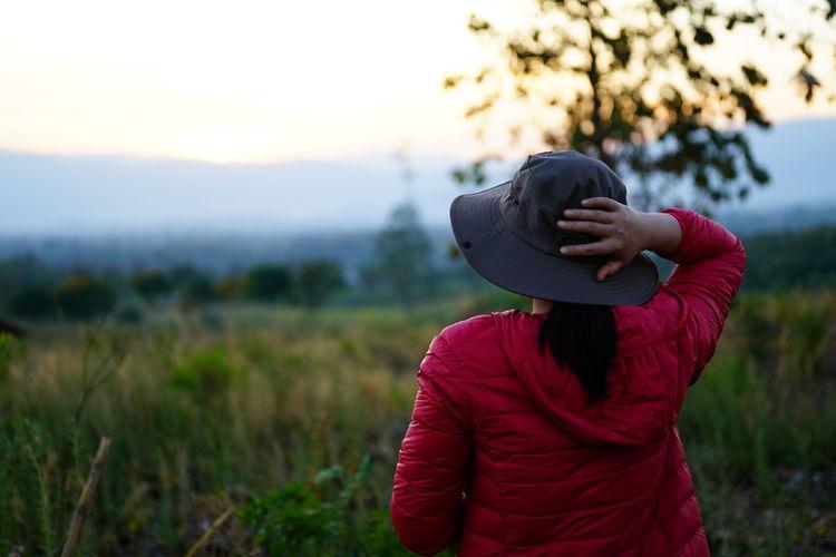 Full length of woman wearing hat standing on field