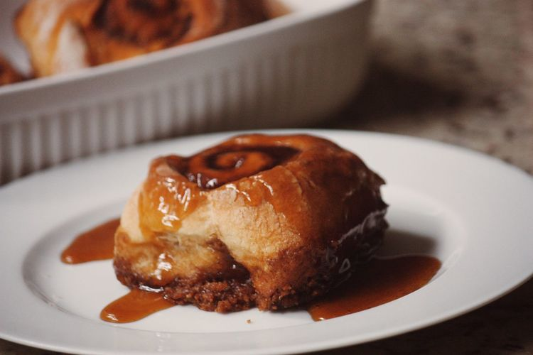 Close-Up Of Cinnamon Roll With Honey In Table
