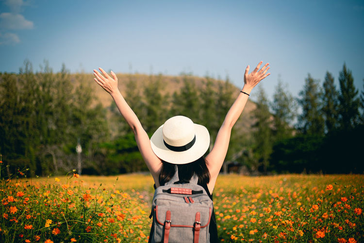 Woman standing by flowering plants on field