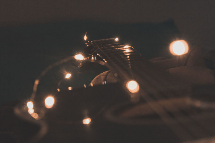 Close-up of illuminated lights against sky at night