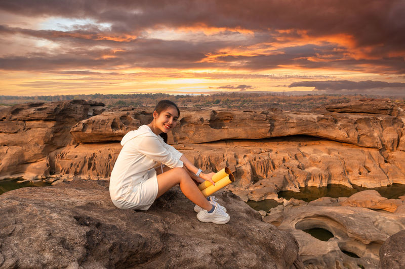 Woman sitting on rock against sky during sunset