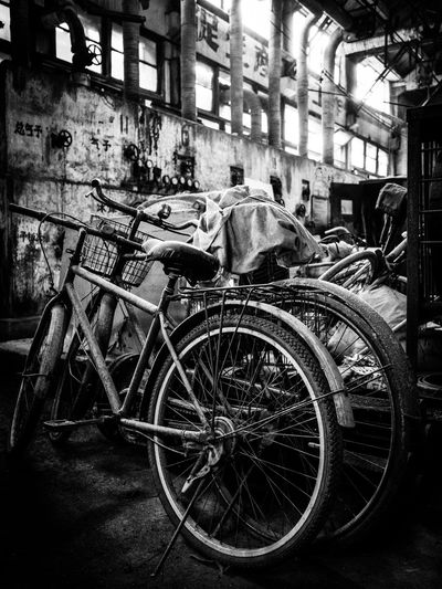 Old bicycle on street against buildings in city