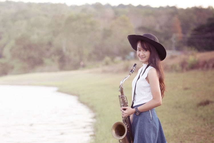 Woman with saxophone with nature background One Person Standing Smiling Leisure Activity Looking At Camera Young Adult Real People Portrait Casual Clothing Hat Lifestyles Three Quarter Length Happiness Water Young Women Clothing Beautiful Woman Women Day Focus On Foreground Hair Hairstyle Outdoors Music Saxophone
