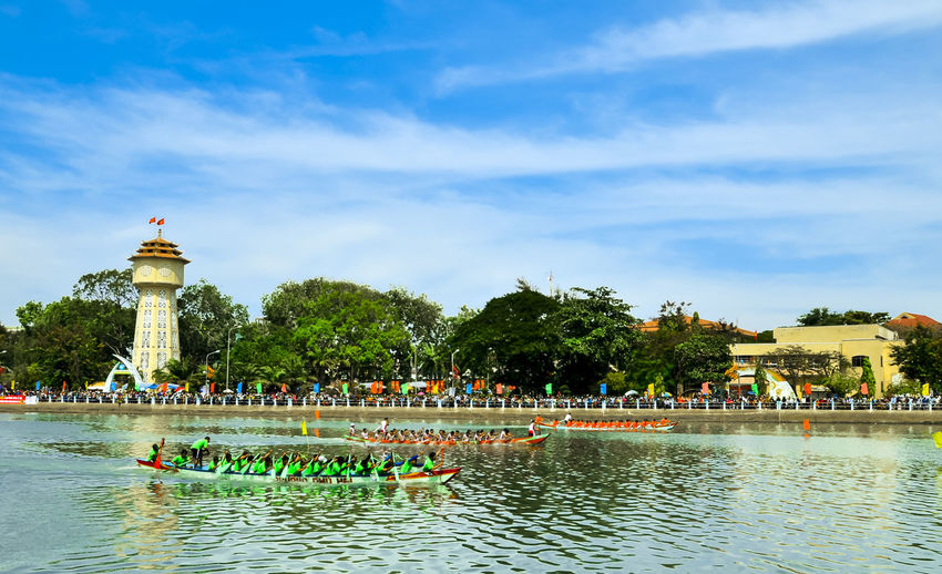 Spring boat racing in Ca Ty river Architecture Blue Built Structure Ca Ty River Cloud Cloud - Sky Cloudy Day Famous Place Large Group Of People Leisure Activity Lifestyles Mixed Age Range Nature Outdoors Phan Thiet Sky Tourism Tourist Travel Destinations Tree Vacations Water