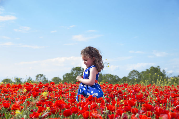 Girl among flowers on field against sky