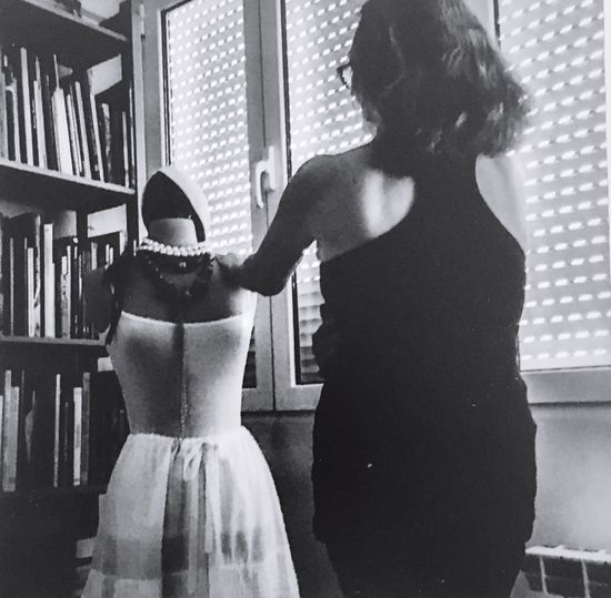 Rear view of women standing at home