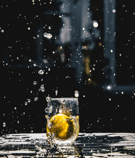 Glass of water splashing on table