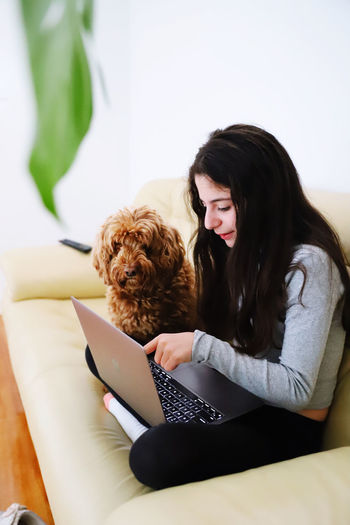 Young woman with dog sitting at home