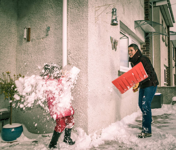 A young girl is covered in snow during a snowball fight with her grand mother Family Building Exterior Built Structure Casual Clothing Childhood Cold Temperature Day Full Length Fun Happiness Humour Leisure Activity Lifestyles Motion Outdoors Playing Real People Smiling Spraying Standing Warm Clothing Winter Young Adult Young Women