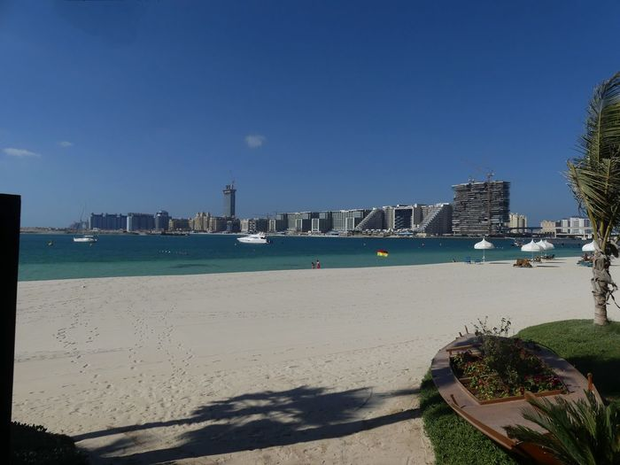 View of The Palm & Atlantis Hotel (left horizon) from the One & Only Hotel, Dubai, United Arab Emirates 2019 Dubai UAE 2019 The Palm Blue Sky No People Water Beach Sea Sunlight And Shadow Sand City Cityscape Villas Modern Architecture Famous Place Boats Building Facades Island Architecture Composition Outdoor Photography Tourist Destination Tourism Travel