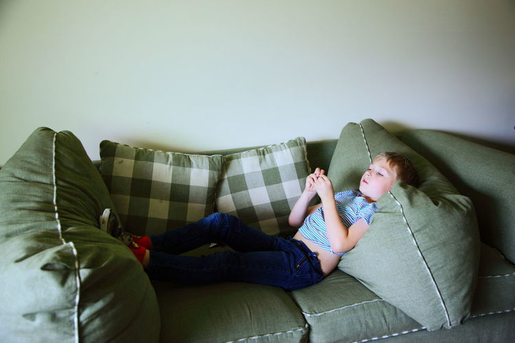 Boy Lying On Sofa Against Wall At Home