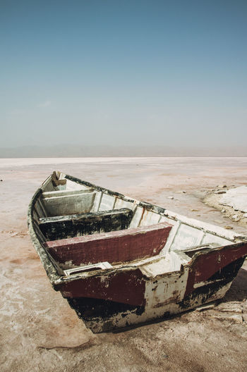 Abandoned boat at beach against sky