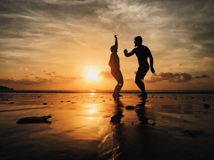 Silhouette friends dancing at beach against sky during sunset
