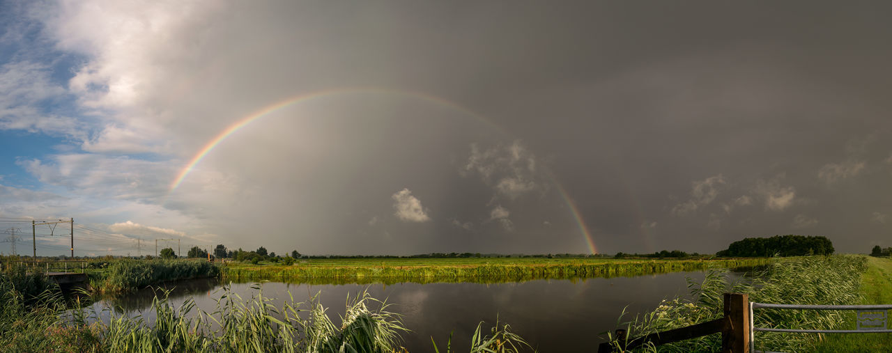 Panoramic view of rainbow over field against sky