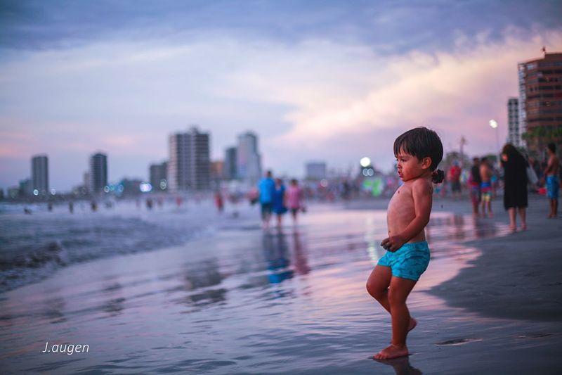 Full length of shirtless man in city against sky during sunset