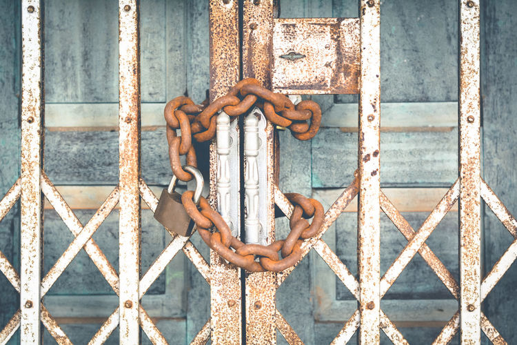 Close-up of padlock and rusty chain wrapped on metallic gate
