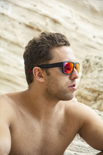 Beach Day Fashion Focus On Foreground Glasses Headshot Land Leisure Activity Lifestyles Mid Adult One Person Outdoors Portrait Real People Sand Shirtless Sunglasses Young Adult Young Men