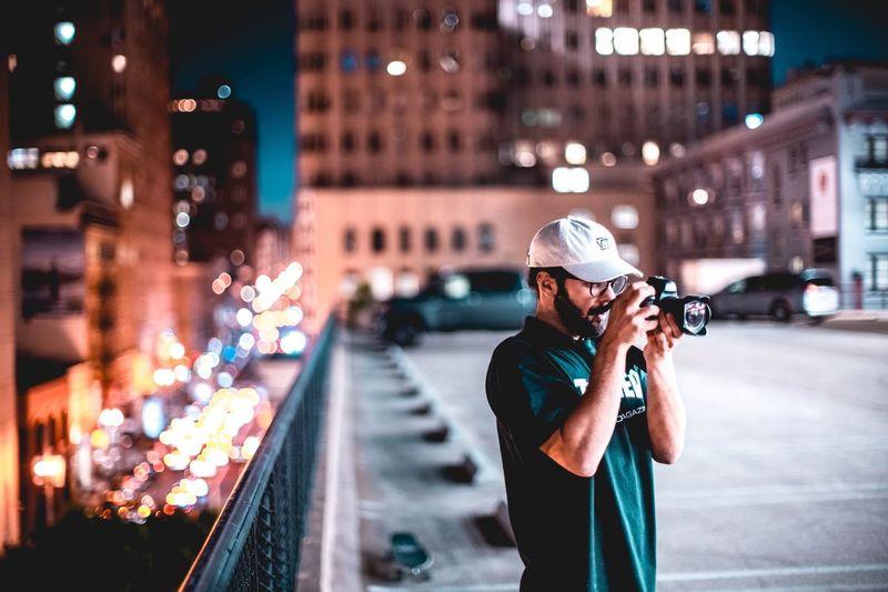Woman photographing illuminated city street at night