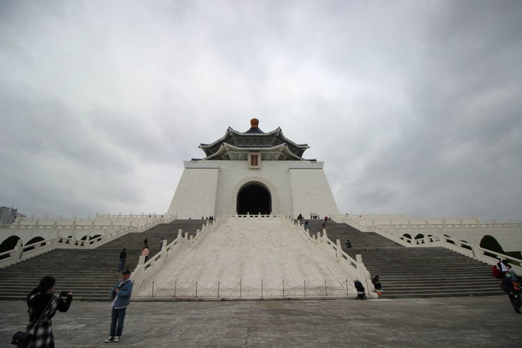 People at historical building against cloudy sky