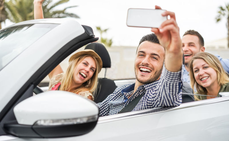 Happy friends taking selfie on convertible car during summer vacation California Camera Driving Friends Happy Miami Palm Travel Young Youth Car Cheerful Convertible Friendship Fun Happiness People Phone Selfie Smartphone Smiling Summer Summer2018 Tropical Vacation