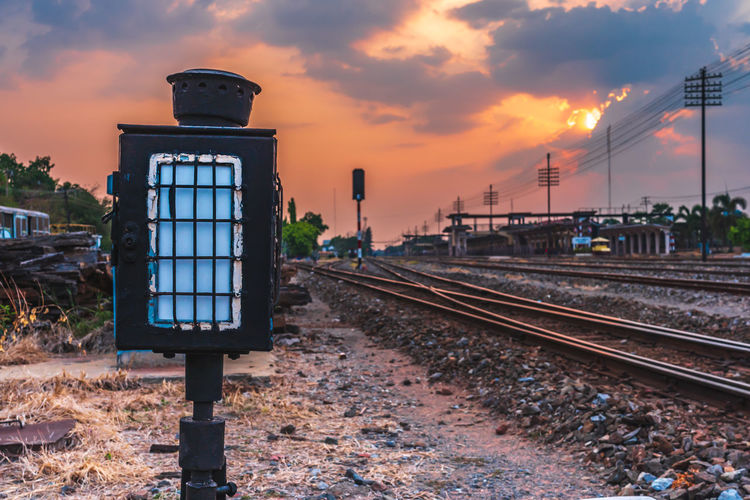 Railroad track amidst field against sky during sunset