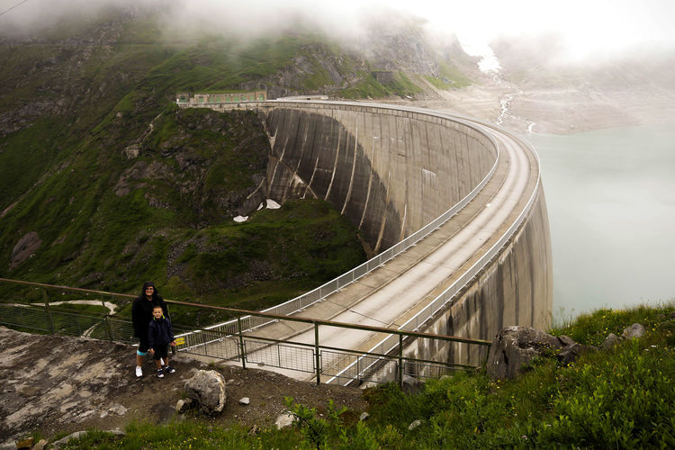 High angle view of woman and child posing on dam