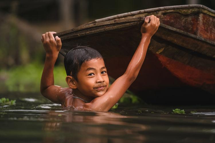 Portrait of boy holding boat in river