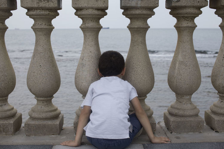 Rear view of boy sitting by balustrade
