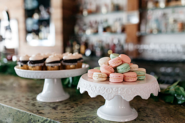 Macaroon and cupcakes on table