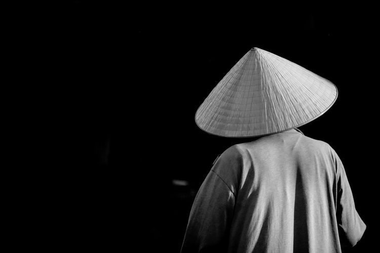 Rear view of man wearing hat standing at night