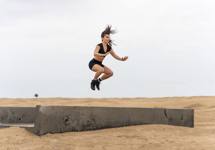 Full length of young woman jumping on beach