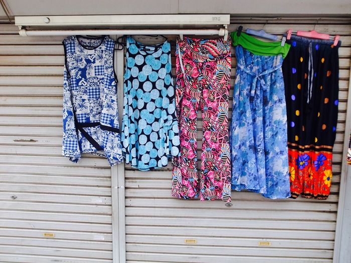 Colorful womenswear hanging on closed shutter