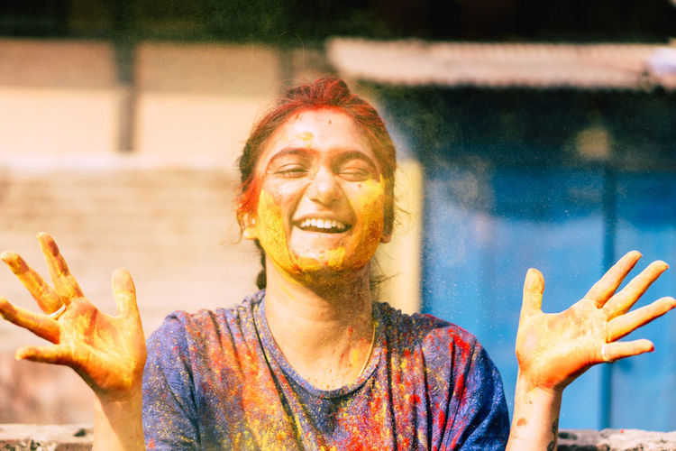 Close-up portrait of happy woman covered with powder paint