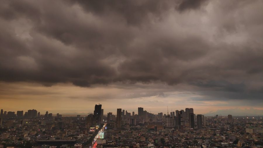 Aerial view of city buildings against storm clouds