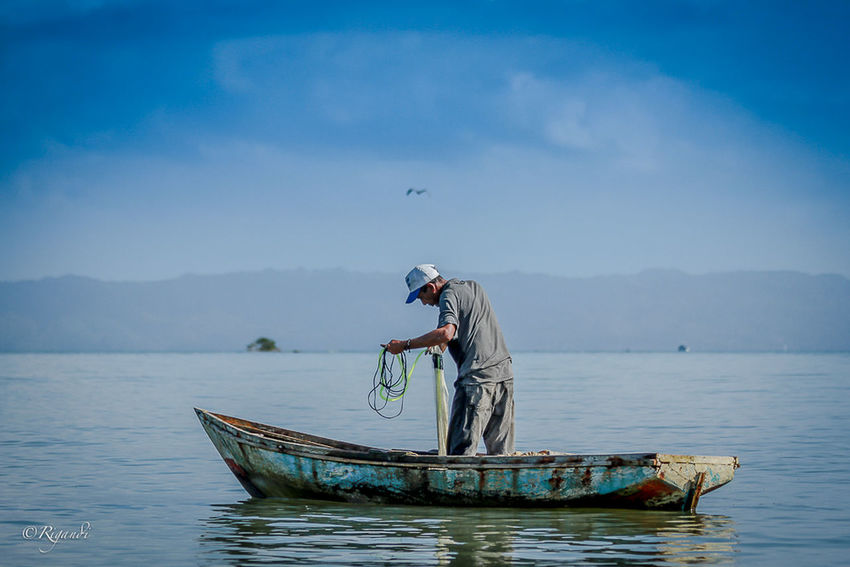 going solo.... Asian Style Conical Hat Beauty In Nature Boat Day Fisherman Fishing Fishing Net Lake Longtail Boat Men Mode Of Transport Mountain Nature Nautical Vessel Occupation One Person Outdoors Real People Scenics Sky Standing Transportation Water Waterfront Wooden Raft The Week On EyeEm