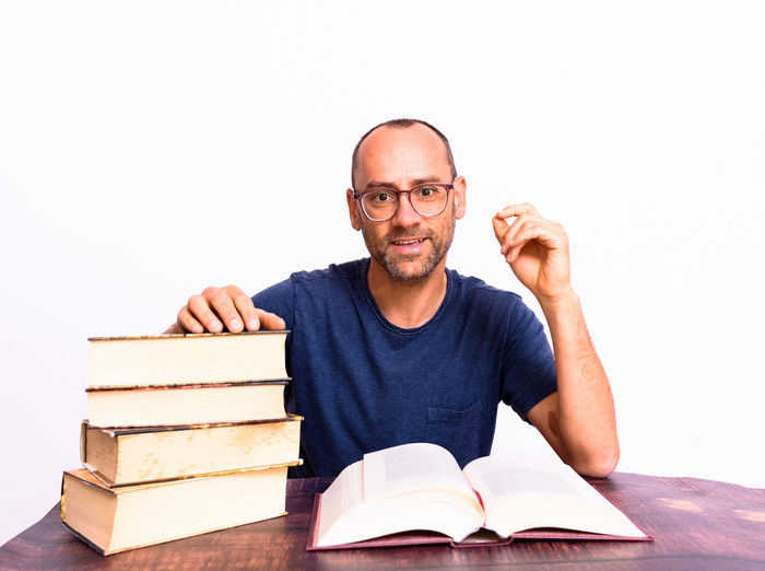 Portrait of young man sitting on book against white background